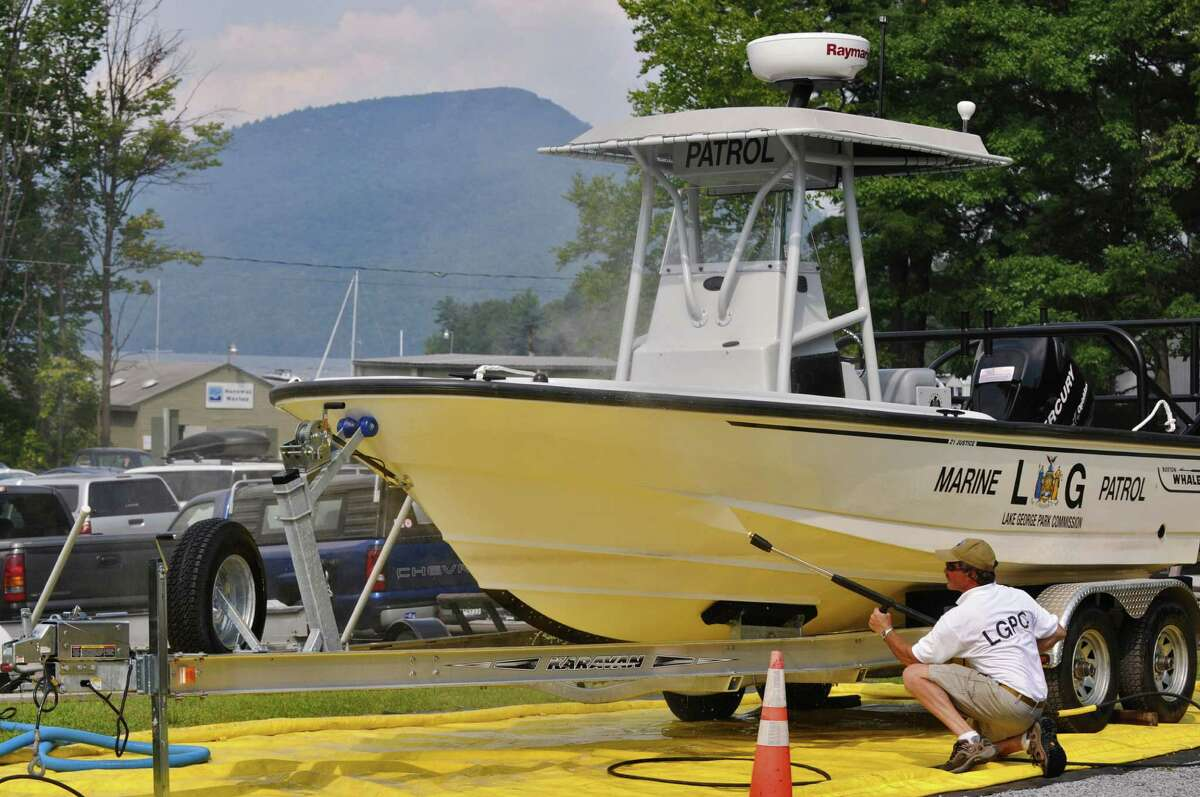 Doug Underhill of The Lake George Park Commission demonstrates how to pressure wash a boat, as the commission is weighing steps to keep invasive species from being brought into the lake by boaters, at Norowal Marina on Thursday Aug. 9, 2012 from Bolton Landing, NY. (Philip Kamrass / Times Union)