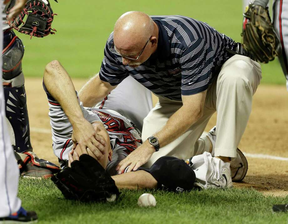 A trainer checks on Tim Hudson after the Braves pitcher's ankle was stepped on while covering first base in the eighth inning of an 8-2 win over the Mets. Hudson has a broken ankle that will require surgery. Photo: Frank Franklin II, STF / AP
