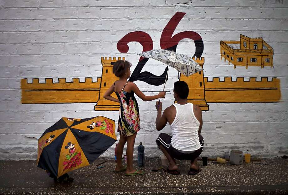 A girl holds an umbrella for her neighbor while he paints a mural to commemorate the 60th anniversary of the attacks of the barracks by the revolutionary forces in Bayamo, Cuba, Wednesday, July 24, 2013. (AP Photo/Ramon Espinosa) Photo: Ramon Espinosa, Associated Press