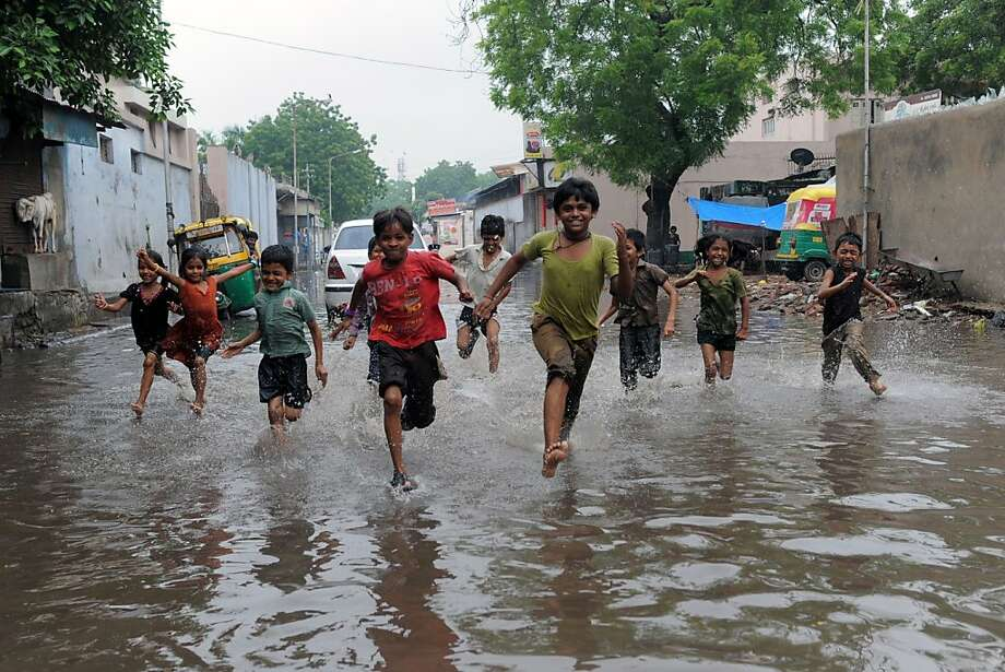 TOPSHOTS Indian children run across a flooded street in Ahmedabad on July 24, 2013. Heavy rains lashed many regions of Gujarat state and the Indian Meteorological Department (IMD) has warned of very heavy rains in Gujarat and surrounding regions in next 36 hours. AFP PHOTO / Sam PANTHAKYSAM PANTHAKY/AFP/Getty Images Photo: Sam Panthaky, AFP/Getty Images