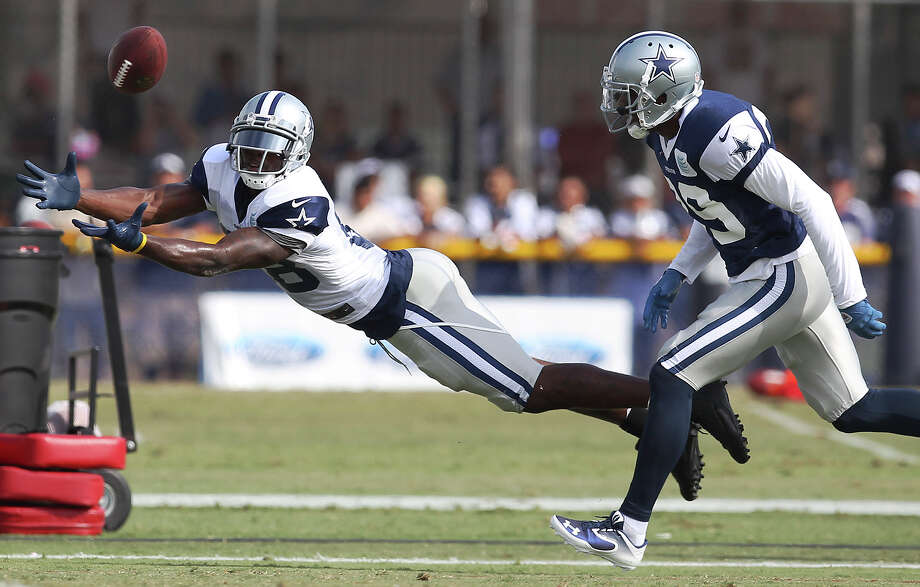 Receiver Dez Bryant dives to attempt a catch against cornerback Brandon Carr (39) during the afternoon session of the 2013 Dallas Cowboys training camp on Wednesday, July 24, 2013 in Oxnard. Photo: Kin Man Hui, San Antonio Express-News / ©2013 San Antonio Express-News