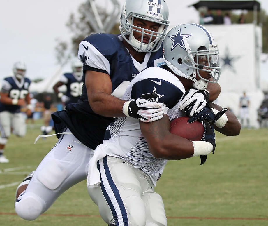 Running back Phillip Tanner (right) gets wrapped up by linebacker Brandon Magee (46) during the afternoon session of the 2013 Dallas Cowboys training camp on Wednesday, July 24, 2013 in Oxnard. Photo: Kin Man Hui, San Antonio Express-News / ©2013 San Antonio Express-News