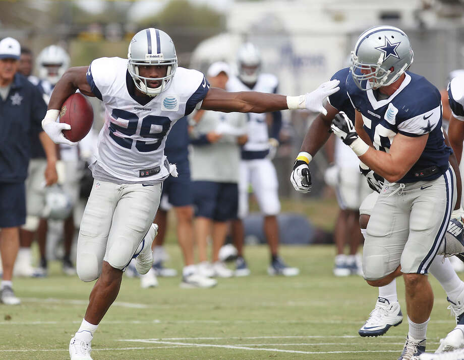 Running back DeMarco Murray extends his arm to linebacker Sean Lee (50) during the afternoon session of the 2013 Dallas Cowboys training camp on Wednesday, July 24, 2013 in Oxnard. Photo: Kin Man Hui, San Antonio Express-News / ©2013 San Antonio Express-News