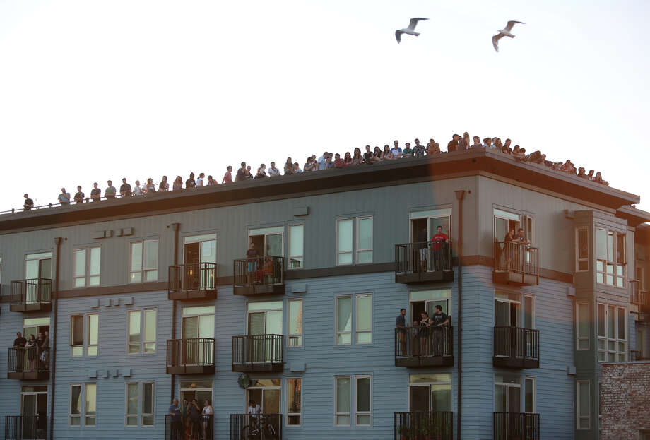 People gather on the roof of an apartment building on Wednesday near the Capitol Hill Dick's Drive-In.  Photo: JOSHUA TRUJILLO, SEATTLEPI.COM / SEATTLEPI.COM