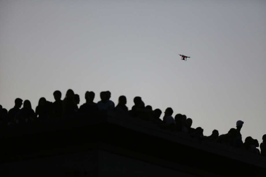 A quad-copter carrying a camera flies over the crowd on Wednesday near the Capitol Hill Dick's Drive-In.  Photo: JOSHUA TRUJILLO, SEATTLEPI.COM / SEATTLEPI.COM