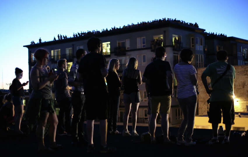 People gather on nearby rooftops on Wednesday at the Capitol Hill Dick's Drive-In. Macklemore and Ryan Lewis were working with a crew to shoot a video for their song