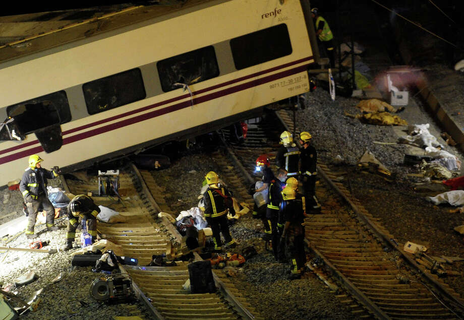 Rescuers work at the site of a train accident as the bodies of the victims, covered with blankets, lie on the ground, near the city of Santiago de Compostela on July 24, 2013. At least 35 people died and 200 people were injured when a train derailed in Galicia in northwestern Spain today, the president of the regional government of Galicia said. The train which carried 238 passengers originated in Madrid and was bound for the northwestern town of Ferrol. Photo: MIGUEL RIOPA, AFP/Getty Images / 2013 AFP