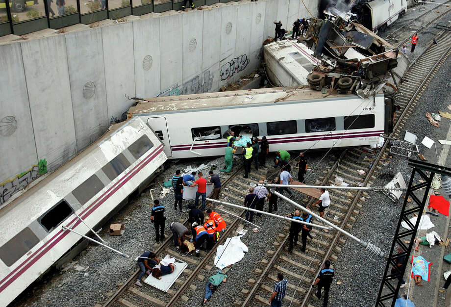 Rescuers tend to victims next to derailed cars at the site of a train accident near the city of Santiago de Compostela on July 24, 2013. Between 45 and 50 people died when a train derailed in Galicia in northwestern Spain today, the president of the regional government of Galicia said. The train which carried 238 passengers originated in Madrid and was bound for the northwestern town of Ferrol. Photo: AFP, AFP/Getty Images / 2013 AFP