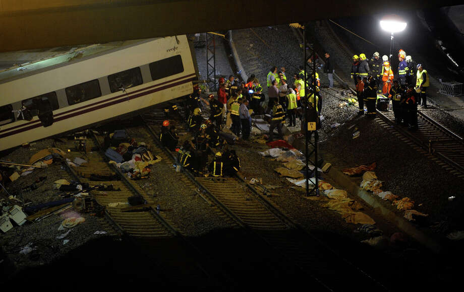 Rescuers, investigators and police officers stand at the site of a train accident near the city of Santiago de Compostela on July 24, 2013. A train hurtled off the tracks in northwestern Spain on July 24 killing 60 passengers and injuring around 130 others, a spokesman for the central government representative in the region said. The train, carrying at least 200 passengers, had left Madrid and was heading for the northwestern town of Ferrol as the Galicia region was preparing celebrations in honor of its patron saint James. Photo: MIGUEL RIOPA, AFP/Getty Images / 2013 AFP