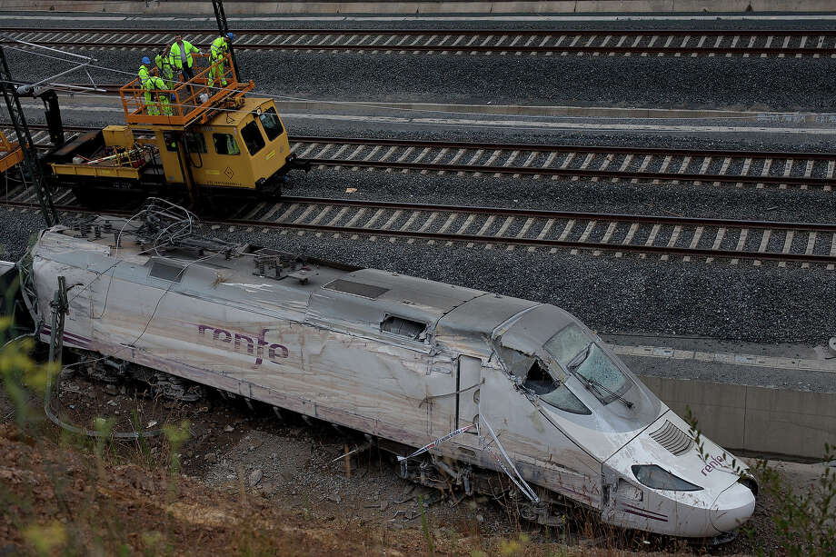 Operators work at the scene of a train crash that killed at least 77 people on July 25, 2013 at Angrois near Santiago de Compostela, Spain. The crash occurred on Wednesday at 8.40pm as the train approached the north-western Spanish city of Santiago de Compostela, with 247 passengers on board.  At least 77 people have died and a further 131 have been reported injured. The crash occurred on the eve of Santiago de Compostela's main religious festival. Photo: Pablo Blazquez Dominguez, Getty Images / 2013 Getty Images
