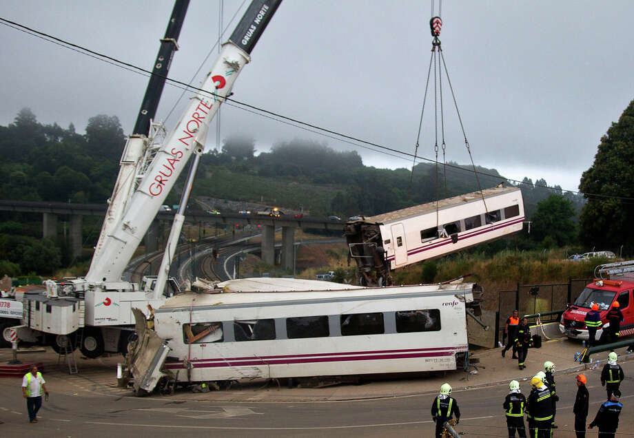 A crane removes a derailed train's car at the site of a train accident near the city of Santiago de Compostela on July 25, 2013. A train hurtled off the tracks on July 24, 2013 in northwest Spain killing at least 77 passengers and injuring more than 140, an official said today, the country's deadliest rail disaster in more than 40 years. Photo: -, AFP/Getty Images / 2013 AFP