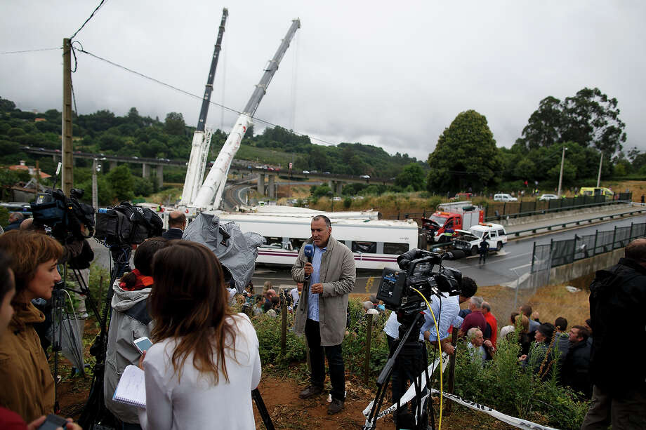 Members of the media report from the scene of a train crash, that killed at least 77 people, on July 25, 2013 at Angrois near Santiago de Compostela, Spain. The crash occurred on Wednesday at 8.40pm as the train approached the north-western Spanish city of Santiago de Compostela, with 247 passengers on board.  At least 77 people have died and a further 131 have been reported injured. The crash occurred on the eve of Santiago de Compostela's main religious festival, which has been cancelled by the City's officials. Photo: Pablo Blazquez Dominguez, Getty Images / 2013 Getty Images
