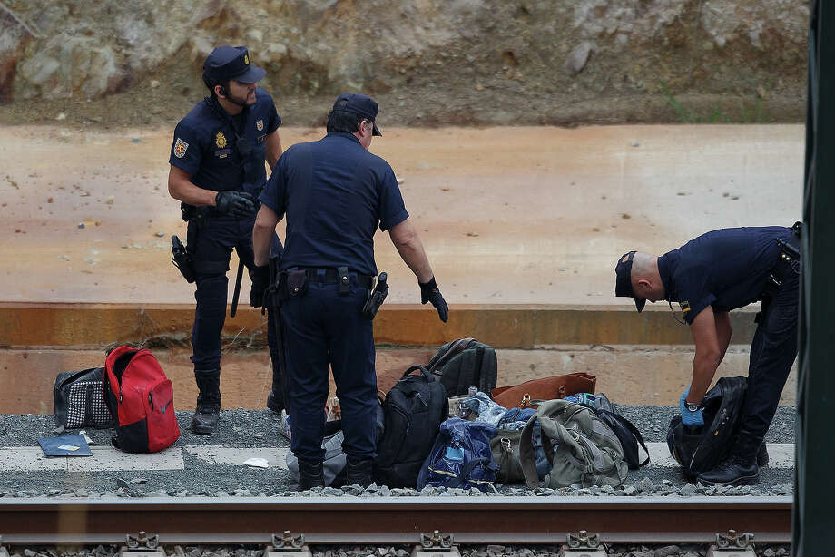 Police officers collect baggage at the scene of a train crash, which killed at least 77 people, on July 25, 2013 at Angrois near Santiago de Compostela, Spain. The crash occurred on Wednesday at 8.40pm as the train approached the north-western Spanish city of Santiago de Compostela, with 247 passengers on board.  At least 77 people have died and a further 131 have been reported injured. The crash occurred on the eve of Santiago de Compostela's main religious festival, which has been cancelled by the City's officials. Photo: Pablo Blazquez Dominguez, Getty Images / 2013 Getty Images