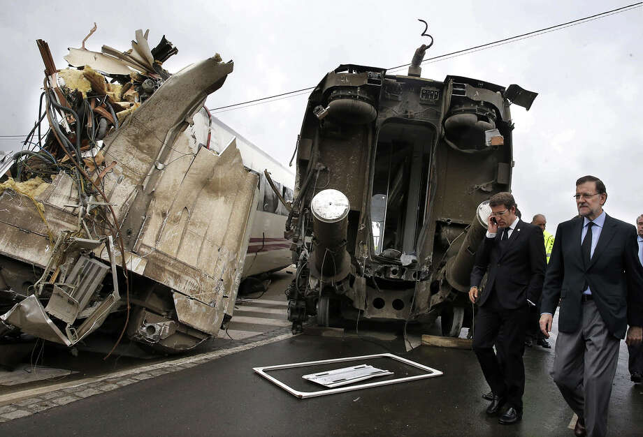 Spanish Prime Minister Mariano Rajoy (R) and Galicia's regional President Alberto Nunez Feijoo (2nd R) visit the site of a train accident near the city of Santiago de Compostela on July 25, 2013. A train hurtled off the tracks on July 24 in northwest Spain killing at least 77 passengers and injuring more than 140, an official said today, the country's deadliest rail disaster in more than 40 years. Photo: AFP, AFP/Getty Images / 2013 AFP
