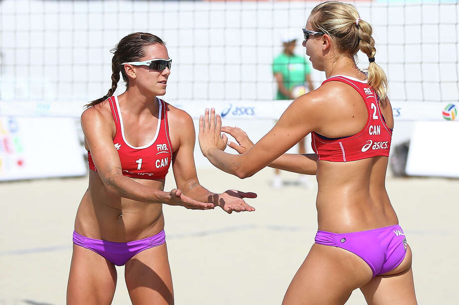 Canadians Jamie Broder (L) and Kristina Valjas celebrate a point at the ASICS World Series of Beach Volleyball - Day 2 on July 23, 2013 in Long Beach, California. Photo: Joe Scarnici, Getty Images / 2013 Getty Images