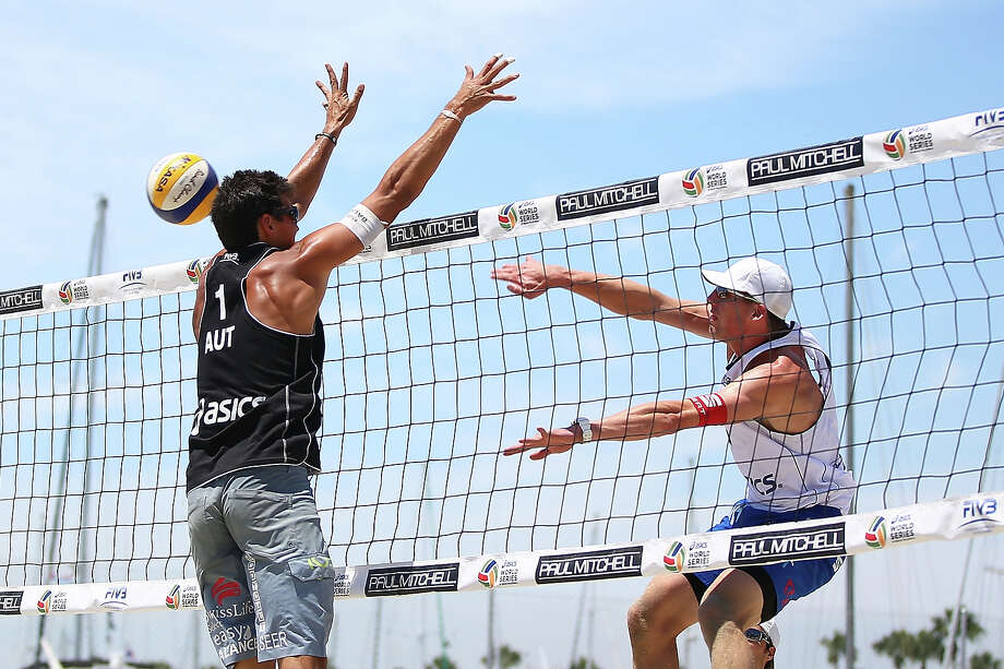 Philip Gabathuler of Switzerland (R) spikes the ball past Peter Eglseer of Austria during the round of pool play at the ASICS World Series of Beach Volleyball - Day 3 on July 24, 2013 in Long Beach, California. Photo: Joe Scarnici, Getty Images / 2013 Getty Images