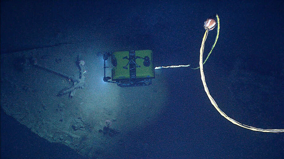 NOAA's Seirios Camera Platform, operating above the Little Hercules ROV, images the ROV and an anchor inside the hull of a copper-sheathed shipwreck in the Gulf of Mexico. The wood has nearly all disintegrated after more than a century on the seafloor.  (Credit: NOAA Okeanos Explorer Program.)