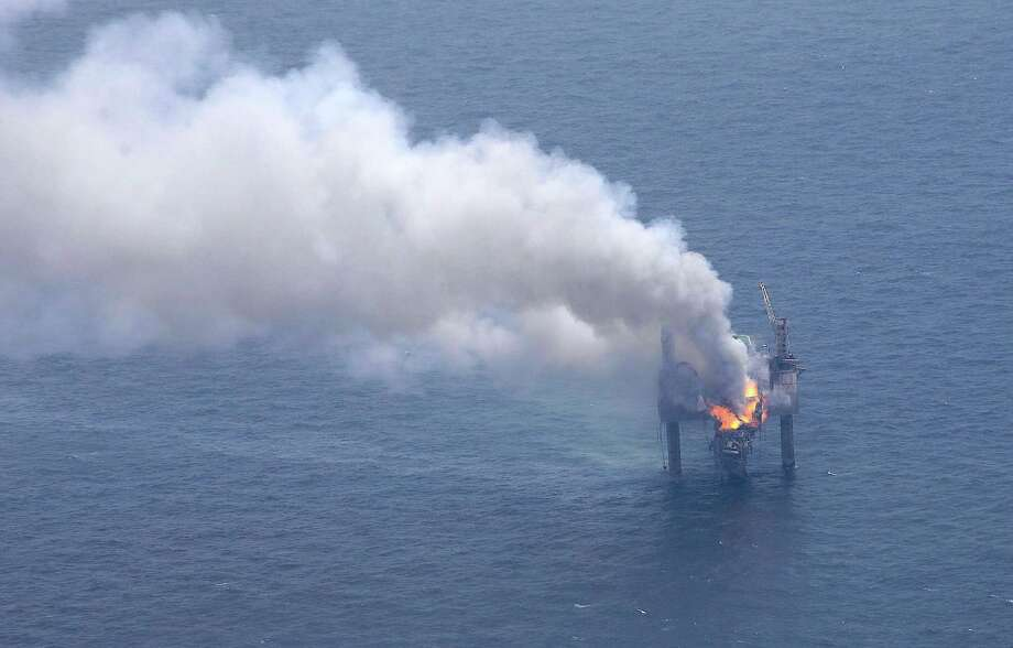 A fire is seen on the Hercules 265 drilling rig in the Gulf of Mexico off the coast of Louisiana, Wednesday, July 24, 2013. Natural gas spewed uncontrolled from the well on Tuesday after a blowout that forced the evacuation of 44 workers aboard the drilling rig, authorities said. No injuries were reported in the blowout. (AP Photo/Gerald Herbert) Photo: Gerald Herbert, STF / AP