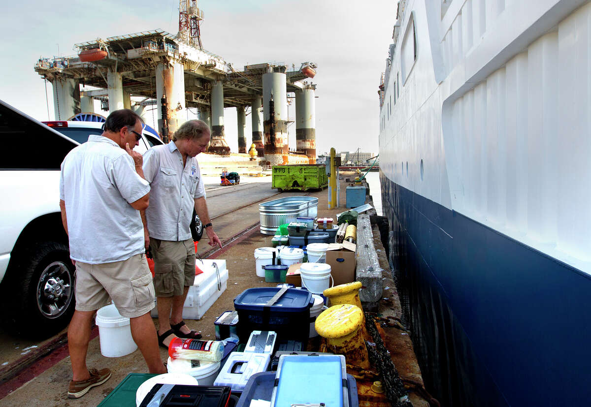 Dr. Steve Gittings, left, and Regional Scientist William Kiene, right, look at artifacts after a crew sailed approximately 170 miles off Galveston to investigate a shipwreck on the Nautilus, Thursday, July 25, 2013, in Galveston. The crew brought back about 60 artifacts and plan to determine the ship's origin from studying the artifacts.