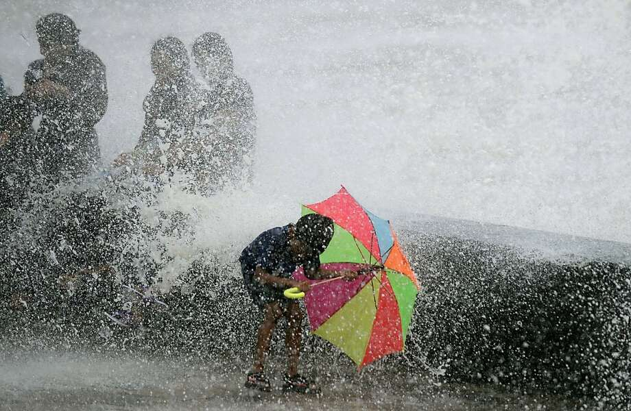 Monsoon by the sea: An umbrella shields a boy from a high-tide wave crashing on the Arabian Sea promenade in 