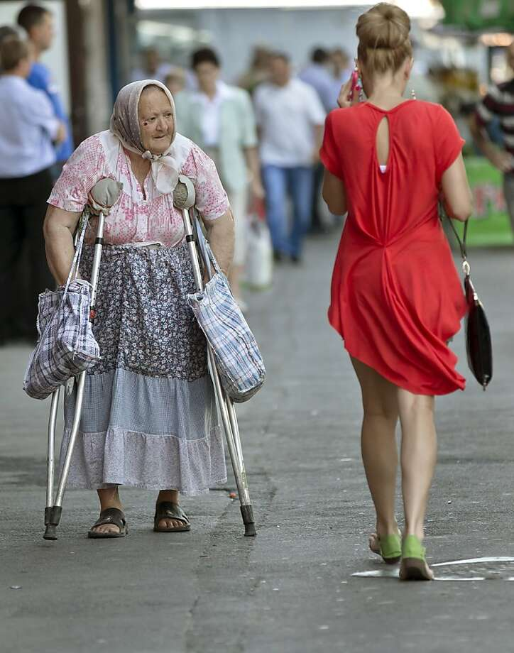 A babushka in Bucharest:An elderly woman on crutches stares across two generations at a fashionable Romanian near the North Railway station. Photo: Vadim Ghirda, Associated Press
