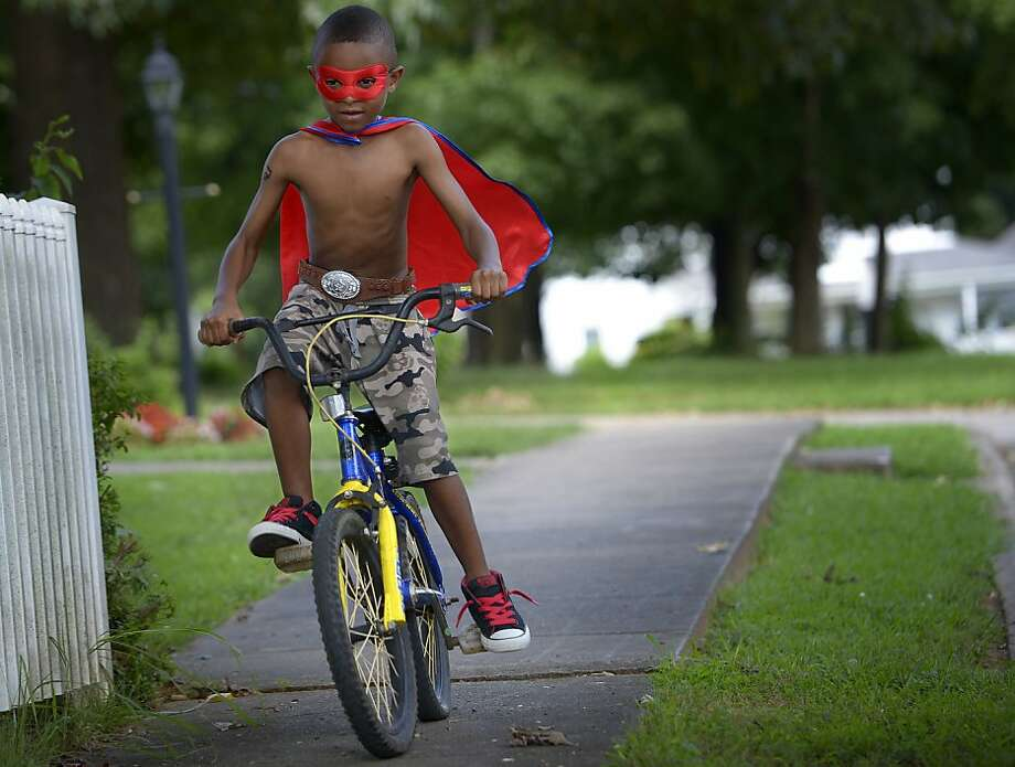 "Don't forget to tie your shoelaces, Cyclon: Six-year-old superhero Oziah Wright, who causes himself ""Cyclon,"" speeds down Climax Street in Graham, N.C., to fight evildoers and defend truth, justice and the American way. Photo: Scott Muthersbaugh, Associated Press"