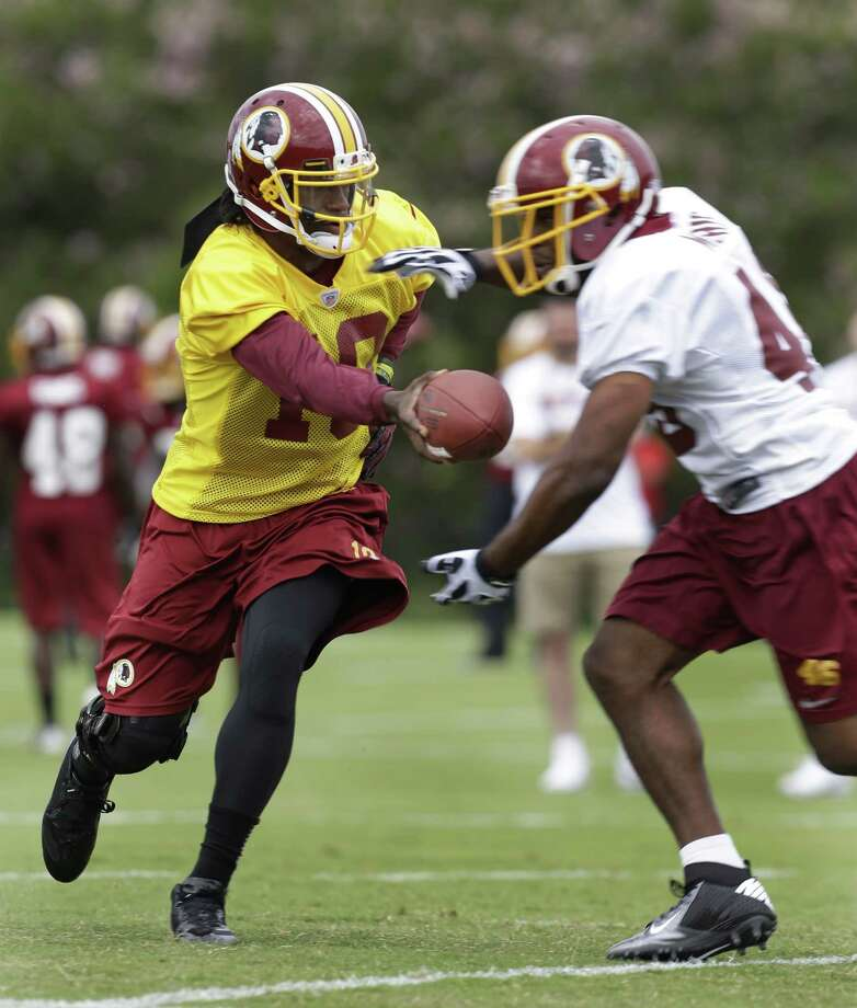 Washington Redskins quarterback Robert Griffin III, left, hands the ball off to Alfred Morris, right, during NFL football training camp in Richmond, Va. Thursday, July 25, 2013.   (AP Photo/Steve Helber) Photo: Steve Helber, Associated Press / AP