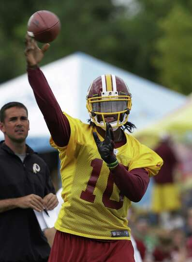 Washington Redskins quarterback Robert Griffin III tosses a pass during NFL football training camp i