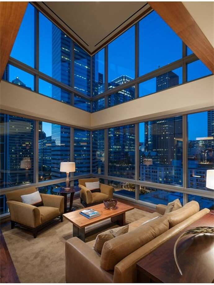 Want a two-story wall of windows overlooking downtown Seattle and Elliott Bay? Check out this condo atop Millennium Tower, 715 2nd Ave., Unit 1504.Noted Seattle architect Jim Olson designed the 3,800-square-foot home, which has master and guest suites that overlook the living room, with sliding privacy partitions, a huge master closet, 2.25 bathrooms, art niche walls of anigre wood, a walnut staircase, a soundproof theater, extra storage and two parking spaces. It's listed for $2.7 million. Photo: Courtesy Julie Biniasz, Realogics Sotheby's International Realty