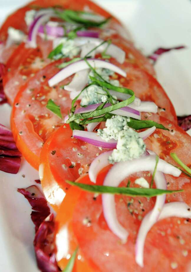 The Brook Tavern. 139 Union Ave., Saratoga Springs.Summer Beefsteak Tomato with red onion, crumbled bleu cheese, basil and vinaigrette on Friday, July 19, 2013, at The Brook Tavern in Saratoga Springs, N.Y. (Cindy Schultz / Times Union) Photo: Cindy Schultz / 00023232A