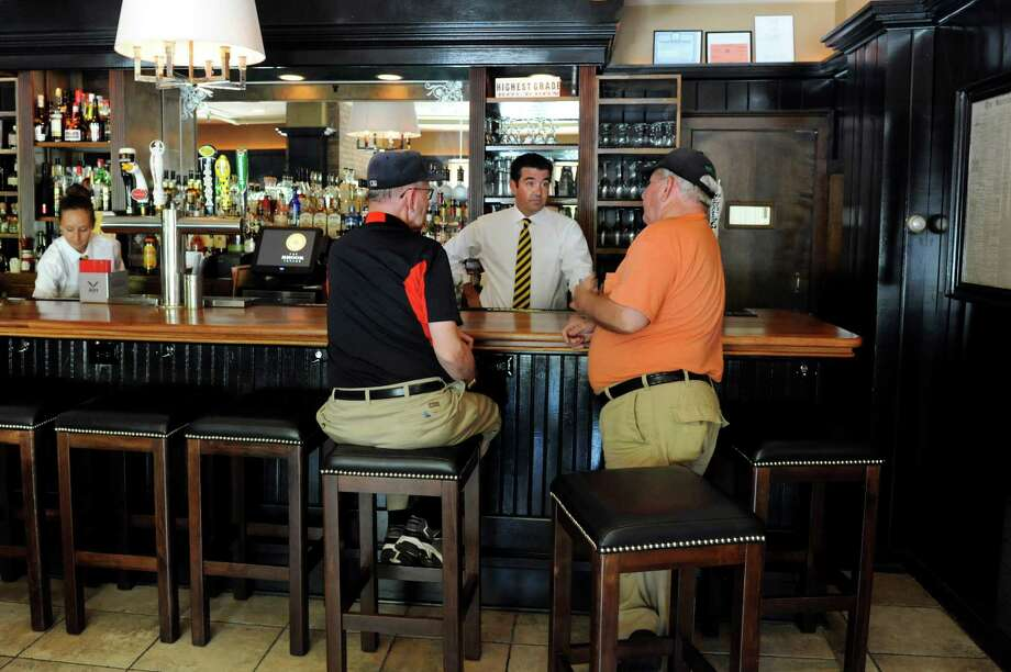 The Brook Tavern. 139 Union Ave., Saratoga Springs.Brothers Robert Fenton, center, and Jack, right, of Naugatuck, Conn. shoot the breeze with bar manager Jim Miller on Friday, July 19, 2013, at The Brook Tavern in Saratoga Springs, N.Y. (Cindy Schultz / Times Union) Photo: Cindy Schultz / 00023232A