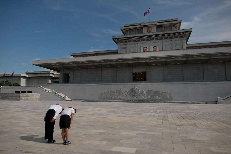 Attendance is mandatory:Two schoolchildren bow before the portraits of 