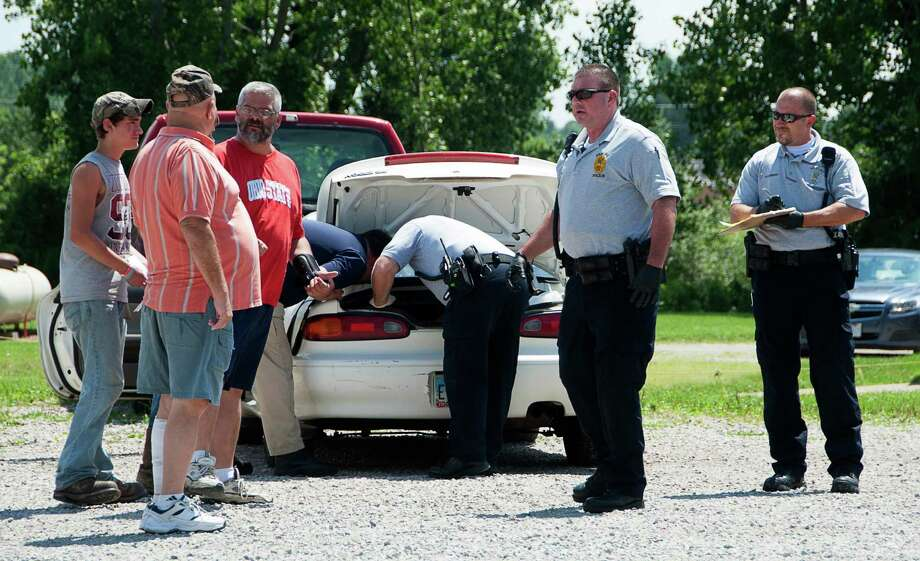 Shelby police investigators searching the trunk of a car in Shelby, Ohio, Tuesday, July 23, 2013.  An Ohio police chief says a 17-year-old told officers that she was the one who gave birth to a baby whose remains were found in a box in the trunk of a car at a repair shop. Photo: News Journal, Dave Polcyn