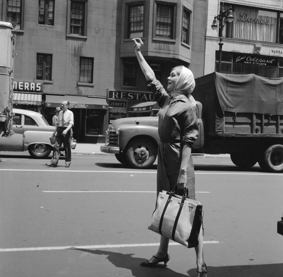 Model Jackie Cahill hails a cab to take her to her next photo assignment for Ford's Model Agency in New York in 1955. Photo: Three Lions, Getty Images