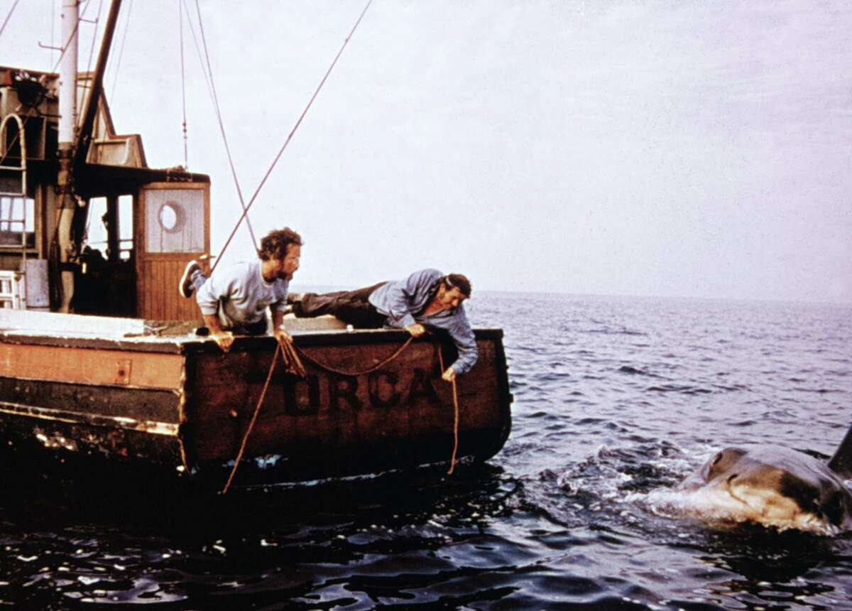 Actors Richard Dreyfuss, left, and the late Robert Shaw hold ropes while leaning off the back of their boat,