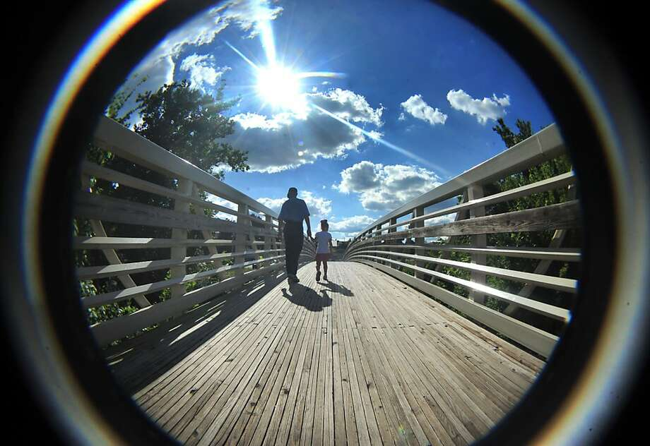 John McKenrick takes his granddaughter, Mia Long, 4, for a stroll across the walking bridge at Chambers Fort Park on a beautiful Thursday afternoon July 25, 2013 in Chambersburg, Pa. The temperatures at 5:30pm hovered around a tropical 75 degrees. The image was captured with a fish-eye lens. (AP Photo/Public Opinion, Markell DeLoatch) Photo:                    Markell DeLoa, Associated Press