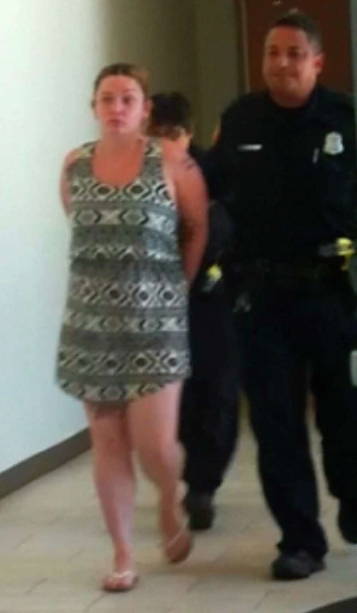 Police escort Breanna Marie Ancira from the city's public safety headquarters after her arrest on Thursday, July 25, 2013. Ancira faces a capital murder charge in the death of Baby Girl Harrison.