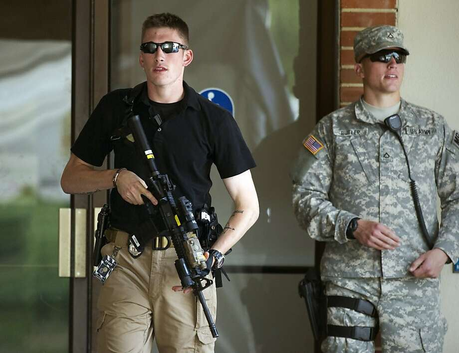 An armed Army Military Police officer carries an automatic rifle out of the courthouse at Fort Mead, Md, where Army Pfc. Bradley Manning is being court martialed, Thursday, July 25, 2013. Manning is charged with indirectly aiding the enemy by sending troves of classified material to WikiLeaks. He faces up to life in prison. (AP Photo/Cliff Owen) Photo: Cliff Owen, Associated Press