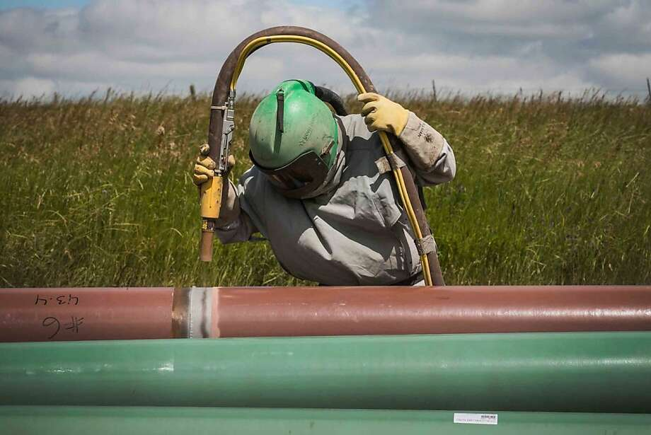 A construction worker specializing in pipe-laying sandblasts a section of pipeline on July 25, 2013 outside Watford City, North Dakota. North Dakota is currently experiencing an oil boom, creating thousands of jobs throughout the state and billions of dollars in new state revenue. Local two-lane roads that are used to access drill sites have taken a beating due to the unprecedented amount of traffic. Pipelines are being constructed across the state in part to streamline the movement of oil from drill sites to train depots and oil refineries.  (Photo by Andrew Burton/Getty Images) Photo: Andrew Burton, Getty Images