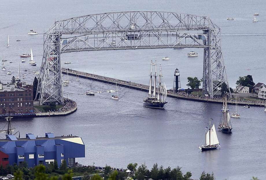 Three tall ships ender the ship canal from Lake superior as they head for the Duluth harbor after passing under the lift bridge  during the parade of tall ships festival Thursday, July 25, 2013. in Duluth, Minn. (AP Photo/Jim Mone) Photo: Jim Mone, Associated Press