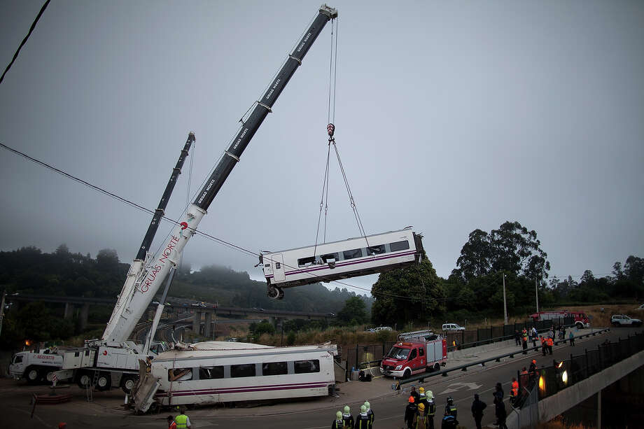 A carriage is lifted at the scene of a train crash on July 25, 2013 at Angrois near Santiago de Compostela, Spain. The crash occurred on Wednesday at 8.40pm as the train approached the north-western Spanish city of Santiago de Compostela, with 247 passengers on board.  At least 77 people have died and a further 131 have been reported injured. The crash occurred on the eve of Santiago de Compostela's main religious festival, which has been cancelled by the City's officials. Photo: Pablo Blazquez Dominguez, Getty Images / 2013 Getty Images