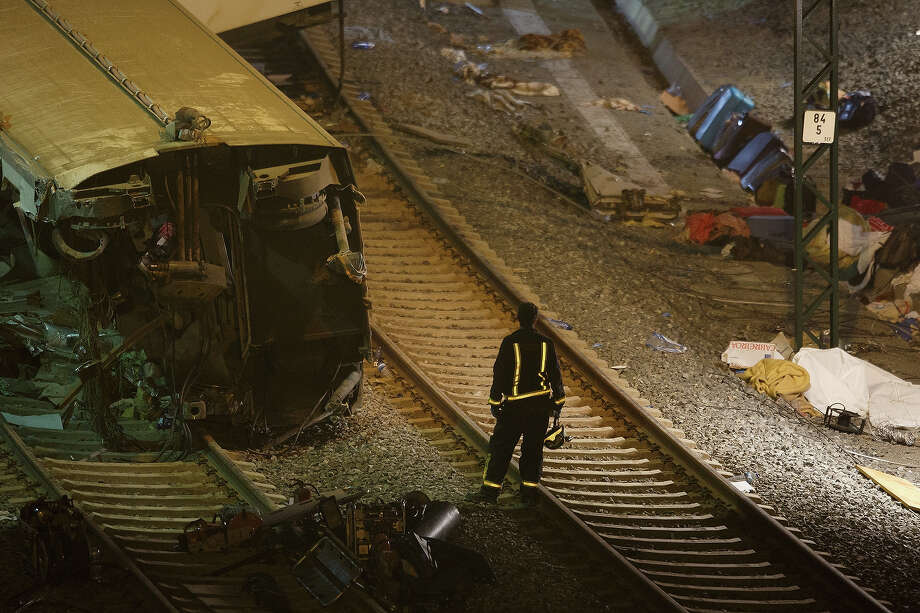 A firefighter works at the scene of a train crash that killed at least 77 people on July 25, 2013 at Angrois near Santiago de Compostela, Spain. The crash occurred on Wednesday at 8.40pm as the train approached the north-western Spanish city of Santiago de Compostela, with 247 passengers on board.  At least 77 people have died and a further 131 have been reported injured. The crash occured on the eve of Santiago de Compostela's main religious festival. Photo: Pablo Blazquez Dominguez, Getty Images / 2013 Getty Images