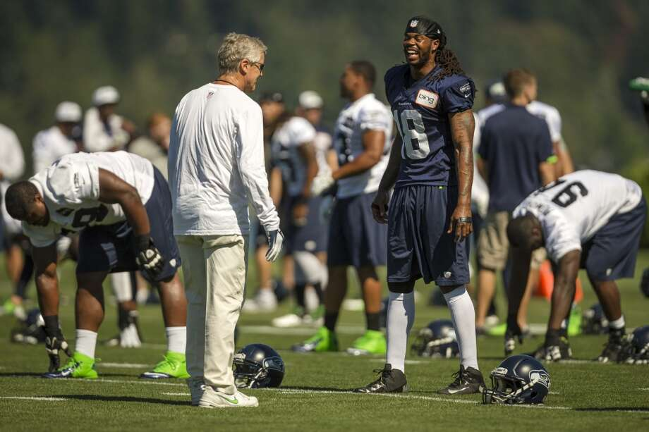 Head coach Pete Carroll, left, jokes with Sidney Rice, right, during the opening day of the Seattle Seahawks training camp Thursday, July 25, 2013, at the Virginia Mason Athletic Center in Renton. The sold-out training camp runs through the preseason in August. Nearly 25,000 fans are expected to attend this month. (Jordan Stead, seattlepi.com) Photo: SEATTLEPI.COM