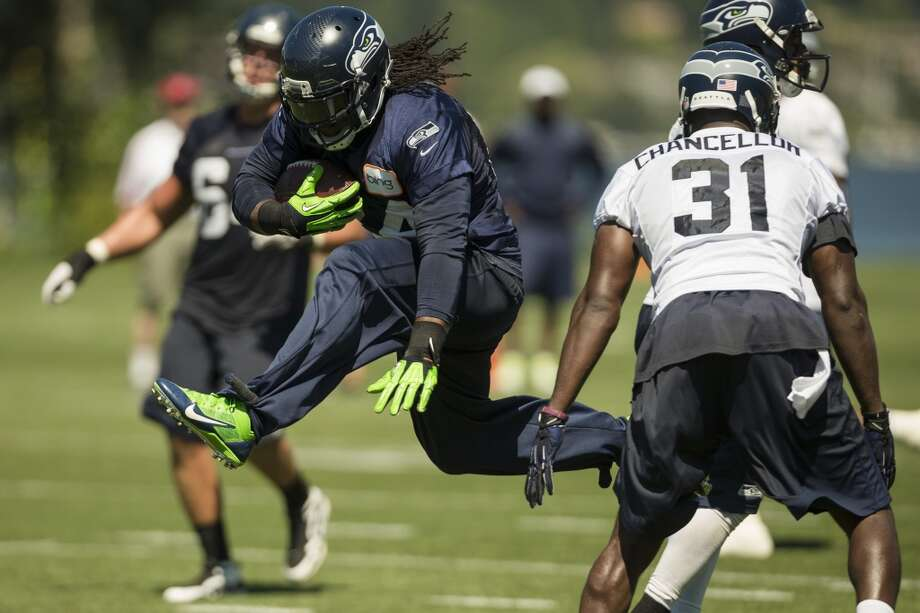 Marshawn Lynch, center, leaps through a defensive line during a drill at the opening day of the Seattle Seahawks training camp Thursday, July 25, 2013, at the Virginia Mason Athletic Center in Renton. The sold-out training camp runs through the preseason in August. Nearly 25,000 fans are expected to attend this month. (Jordan Stead, seattlepi.com) Photo: SEATTLEPI.COM