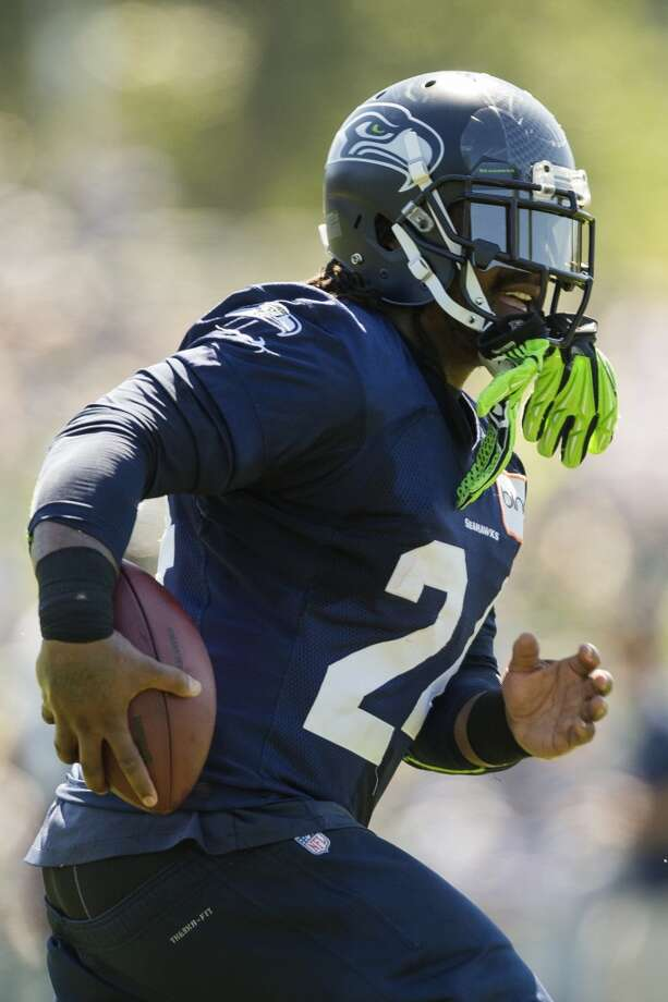 Marshawn Lynch, with gloves dangling from his helmet, runs a drill at the opening day of the Seattle Seahawks training camp Thursday, July 25, 2013, at the Virginia Mason Athletic Center in Renton. The sold-out training camp runs through the preseason in August. Nearly 25,000 fans are expected to attend this month. (Jordan Stead, seattlepi.com) Photo: SEATTLEPI.COM