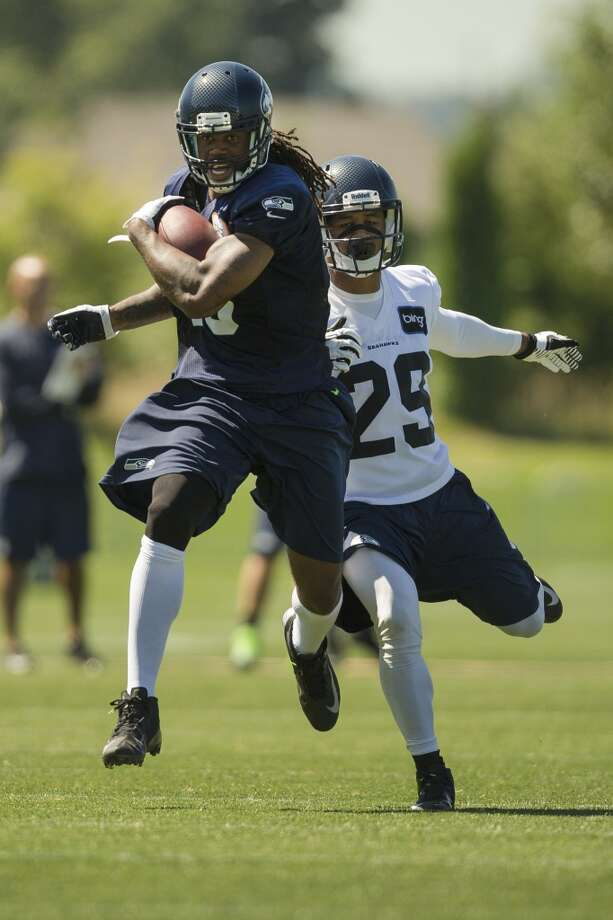 Sidney Rice, foreground, runs past Earl Thomas, background, during an offensive drill at the opening day of the Seattle Seahawks training camp Thursday, July 25, 2013, at the Virginia Mason Athletic Center in Renton. The sold-out training camp runs through the preseason in August. Nearly 25,000 fans are expected to attend this month. (Jordan Stead, seattlepi.com) Photo: SEATTLEPI.COM