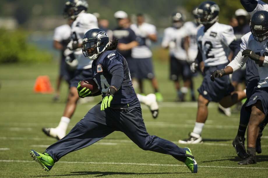 Marshawn Lynch, center, strides through a midfield defensive line during a drill at the opening day of the Seattle Seahawks training camp Thursday, July 25, 2013, at the Virginia Mason Athletic Center in Renton. The sold-out training camp runs through the preseason in August. Nearly 25,000 fans are expected to attend this month. (Jordan Stead, seattlepi.com) Photo: SEATTLEPI.COM