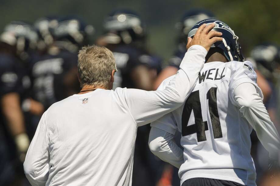 Head coach Pete Carroll, left, gives Byron Maxwell, right, a pat on the helmet following the completion of a drill at the opening day of the Seattle Seahawks training camp Thursday, July 25, 2013, at the Virginia Mason Athletic Center in Renton. The sold-out training camp runs through the preseason in August. Nearly 25,000 fans are expected to attend this month. (Jordan Stead, seattlepi.com) Photo: SEATTLEPI.COM