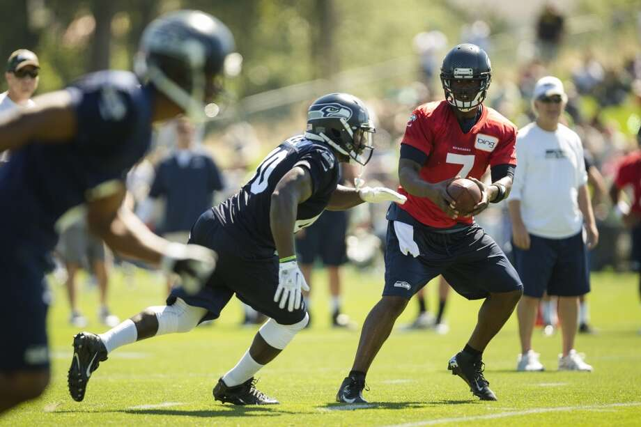 Quarterback Tarvaris Jackson, right, hands off to a teammate during a drill at the opening day of the Seattle Seahawks training camp Thursday, July 25, 2013, at the Virginia Mason Athletic Center in Renton. The sold-out training camp runs through the preseason in August. Nearly 25,000 fans are expected to attend this month. (Jordan Stead, seattlepi.com) Photo: SEATTLEPI.COM