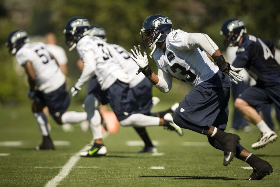 Phil Bates, right, runs alongside teammates during a drill at the opening day of the Seattle Seahawks training camp Thursday, July 25, 2013, at the Virginia Mason Athletic Center in Renton. The sold-out training camp runs through the preseason in August. Nearly 25,000 fans are expected to attend this month. (Jordan Stead, seattlepi.com) Photo: SEATTLEPI.COM
